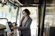 Female Passenger In Face Mask Paying Bus Fare With Smart Phone