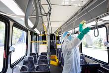 Male Worker In Clean Suit Sanitizing Public Bus