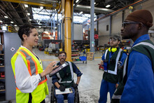 Transit Supervisor Talking With Workers In Maintenance Facility