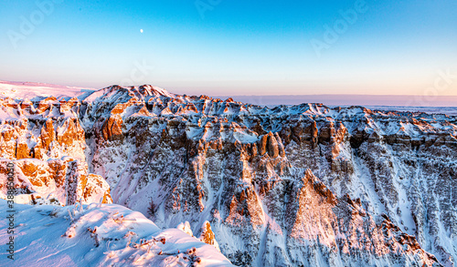 Fotografia Snow covered ridges in Badlands National Park illuminated by the Golden Hour of