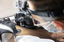 Tattoo Artist At Work On Custo...