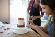 Teen Girl Decorating Cake