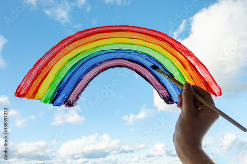 Fotografie, Obraz Kid hand painting colorful rainbow on window during Covid-19 quarantine at home