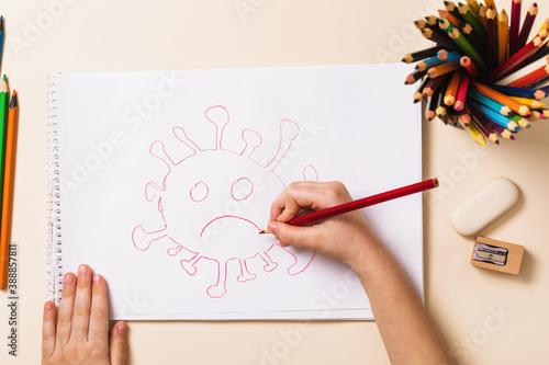 A small child in quarantine draws a coronavirus bacterium, top view Wallpaper Mural