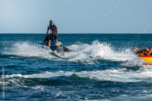 Fototapeta A jet ski at high speed pulls an inflatable boat with a passenger