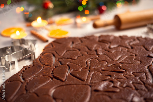 Obraz Brown chocolate dough, shaped in cookies of various form, lays on the table. Christmas decoration on the background. - fototapety do salonu