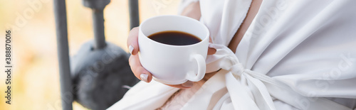 cropped view of woman in white robe drinking coffee on balcony, horizontal banne Canvas Print