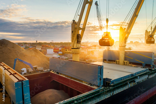 Photo Large international transportation vessel in the port, loading grain during sunrise for export in the sea waters