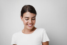 Happy Young Woman Smiling Wearing White T-shirt Looking Down. Space For Text.