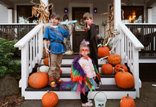 Typical American Kids In Homemade Costumes On Halloween Posing On Their Front Porch