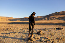 A Young Girl In Black Tight-fitting Clothes With A Beautiful Figure Stands On A Stone In The Middle Of A Huge Desert With Mountains At Sunset