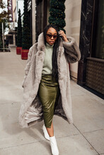 Woman Wearing Grey Fur Coat And A Green Outfit Walking In Shopping District