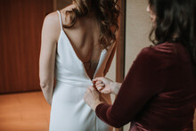 Maid Of Honor Zipping Up Bride...