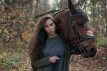 Photo Of A Dark-skinned Girl With Long Curly Hair With Her Brown Horse In Nature