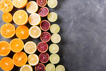 Different Citrus Fruit On Gray Concrete Table. Whole And Sliced Fruit. Food Background. Healthy Eating And Diet. Citrus Fruits. Slices Of Orange, Lemon, Grapefruit, Mandarin, Lime. Copyspace