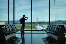 Traveler In Airport, Silhouette Of Backpacker Waiting For The Flight, People Traveling