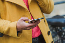 Close Up Of Hands Using Mobile Internet On Smart Phone, Woman With Smartphone Wearing Yellow Coat