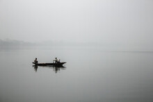 Two Anonymous Fishermen On A Boat On A Lake In Fog In Ha Noi, Vietnam