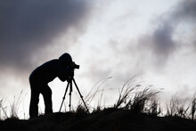 Silhouette Of A Photographer With A Tripod Against The Sky With Clouds