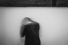 A Mental Health Concept Of A Blurred, Hooded Figure Looking Down, With His Head In His Hands.