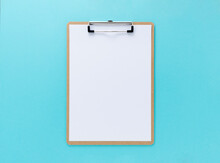 A Clipboard With White Paper On A Blue Background
