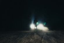 A Sinister Hooded Figure, Silhouetted Against Car Headlights