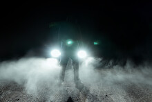 A Spooky Hooded Figure, Silhouetted Against Car Headlights
