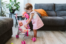 Cute Baby Girl Putting Toys In Baby Stroller While Standing At Home