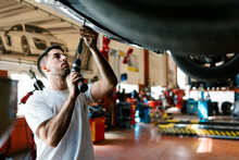 Young Mechanic Repairing Car W...