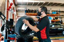 Mechanic Wearing Mask Examining Tire In Auto Repair Shop