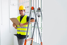 Smiling Architect Leaning While Standing By Ladder At Office Under Construction