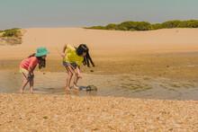 Sisters Fishing Crabs In Sea W...