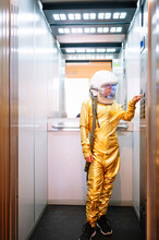 Boy Wearing Space Suit Pressing Buttons In Open Elevator