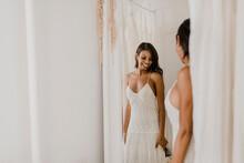 Smiling Bride Looking In Mirro...