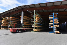 Forklift Standing In Front Of Planks Stored On Warehouse Rack