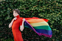 Non-binary Person In Red Dress Holding Rainbow Flag While Standing Against Ivy Wall