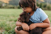Boy Sitting With Dog On Grass At Backyard