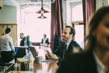 Smiling Male Entrepreneur Using Phone In Restaurant