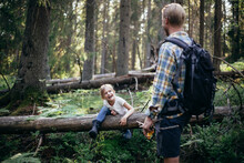 Smiling Daughter Climbing Over Fallen Tree While Looking At Father In Forest