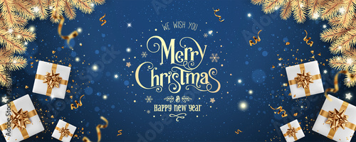 Obraz Gold Merry Christmas and New Year text on blue holiday background with gold gift boxes, fir branches, ribbons, decoration, sparkles, confetti, bokeh, light. Xmas card. Vector Illustration - fototapety do salonu
