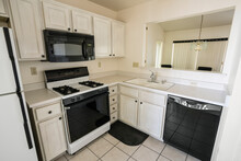 Clean 1990s Style Suburban Condo Kitchen With Light Colored Cabinets And Tile Floor.