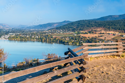 Fotografie, Obraz view from behind a wooden, log fence of the lake and hills covered with green tr