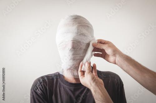 Photo Man makes bandage in injured man. Trauma of the head