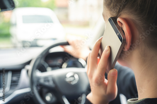 Fotografiet Woman looking at mobile phone while driving a car