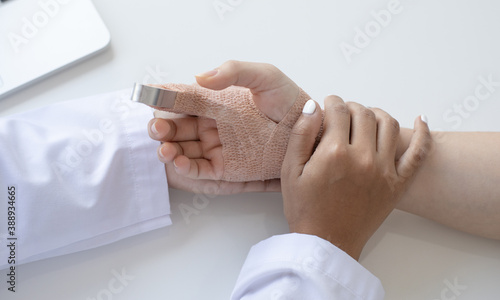 Canvastavla Doctor is examining a patient who has a finger splint in the examination room
