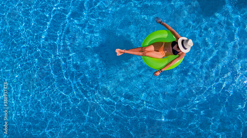 Fotografia Beautiful woman in hat in swimming pool aerial view from above, young girl relax