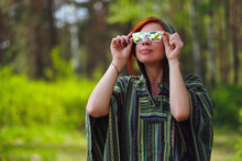 A Young Hippie Girl With Bright Red Hair In A Poncho Against The Green Of The Forest. She Looks Into The Distance Through Kaleidoscope Glasses With Multicolored Lenses. Summer Mood