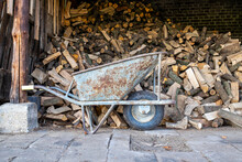 Wheelbarrow In Front Of A Pile Of Fireplace Wood
