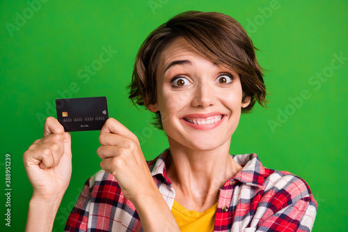 Photo of impressed nice short hairdo girl showing card wear cool cloth isolated over vivid green color background