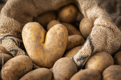 Fotografia Heart-shaped potato and pile of raw potatoes